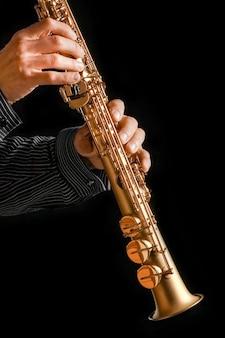Saksofon sopranowy w rękach na czarnej powierzchni