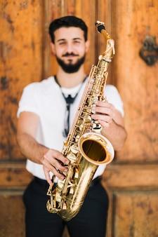 Saksofon trzymany przez nieostrego buźka muzyka