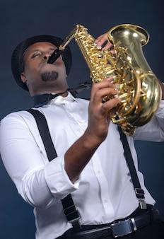 Saksofonista czarny człowiek grający na saksofonie.