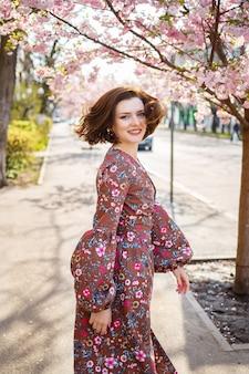 Sakura rozgałęzia się kwiatami na drzewie na ulicach miasta. szczęśliwa kobieta dziewczyna przędzenia na ulicy z kwitnącą sakura. sakura kwitnie.