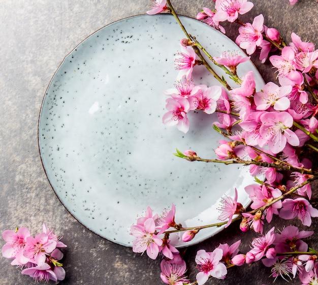 Sakura rozgałęzia się wokół szarego talerza
