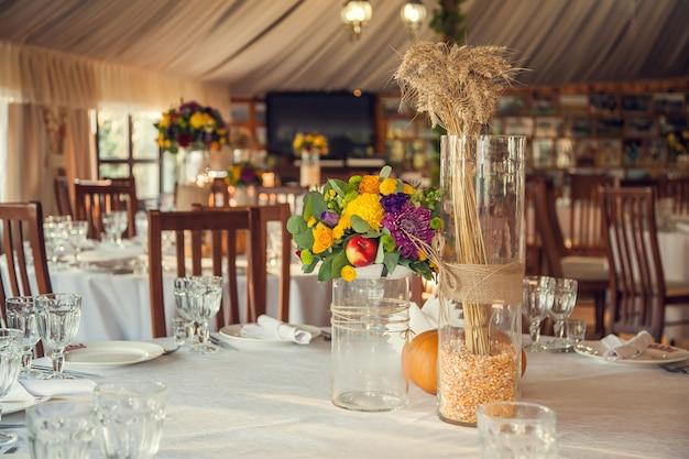 Sala bankietowa udekorowana kwiatami i dyniami w jesiennym stylu. świąteczna florystyka i dekoracja imprez aranżacje florystyczne
