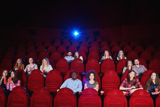 Sala kinowa z widzami siedzącymi i oglądającymi film