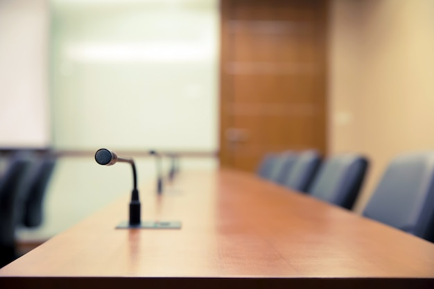 Sala konferencyjna lub sala konferencyjna z profesjonalnym mikrofonem na stole.