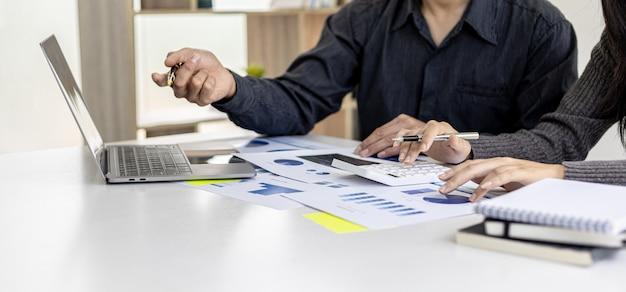 Sala konferencyjna startupu, w której biznesmeni wskazują na ekrany swoich laptopów, aby zobaczyć podsumowania finansowe firmy, spotykają się na comiesięczne tematy finansowe. koncepcja zarządzania finansami