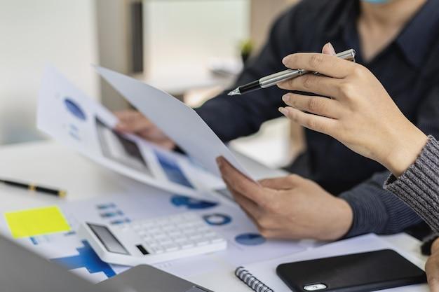 Sala konferencyjna startupu, w której dwóch biznesmenów przegląda informacje finansowe z dokumentów, spotyka się na comiesięczne tematy finansowe. pojęcie zarządzania finansami.