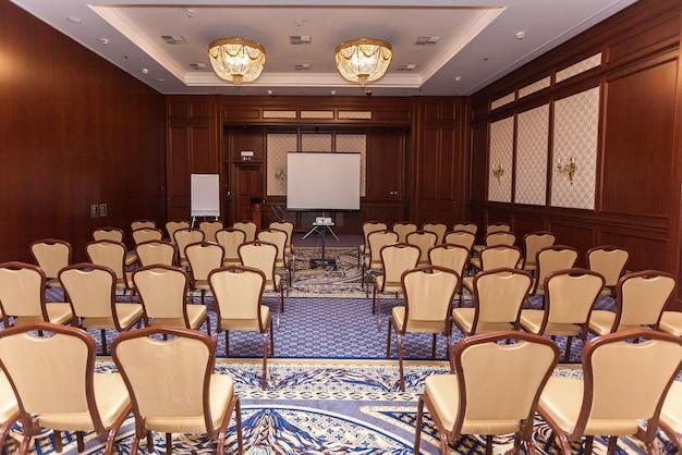 Sala konferencyjna z beżowymi krzesłami i projektorem. przemówienie publiczne. rozmowa z publicznością. klasa mistrzowska. puste wnętrze sali konferencyjnej.