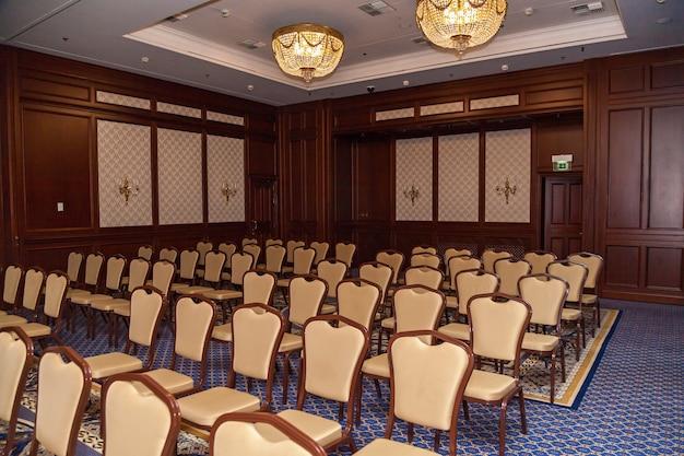 Sala konferencyjna z beżowymi krzesłami i projektorem przemówienie publiczne rozmowa z publicznością master class