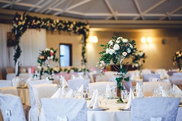 Sala restauracji z stołami zdobionymi wysokimi wazami z różami