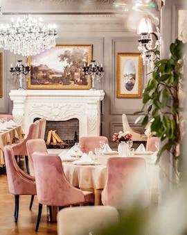 Sala restauracyjna z okrągłym stołem, niektóre krzesła kominek i rośliny