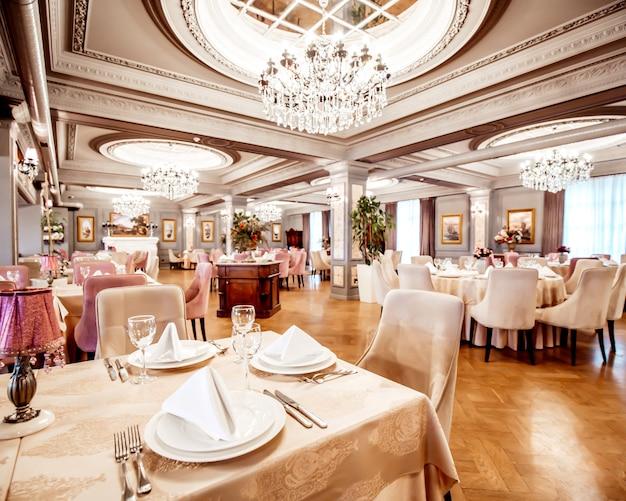 Sala restauracyjna z okrągłymi i kwadratowymi stołami, krzesłami i roślinami