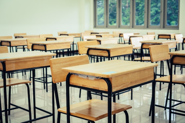 Sala wykładowa lub pusta sala szkolna z biurkami krzesło z żelaznego drewna do nauki lekcji w szkole średniej