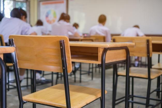 Sala wykładowa lub szkolna pusta sala lekcyjna ze studentem przystępującym do egzaminów, egzamin pisemny