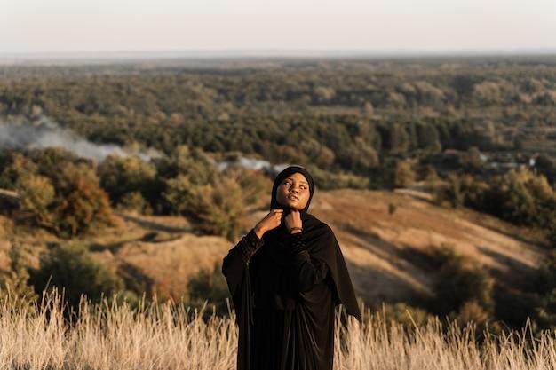 Salah. afrykańska kobieta w czarnej szacie modli się w bogu. religia islamska