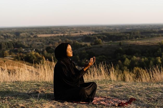 Salah. afrykańska kobieta w czarnej szacie siedzi na dywanie i modli się w bogu. religia islamska