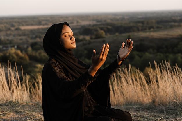 Salah tradycyjna modlitwa do boga na dywanie. czarna muzułmanka modli się do allaha.