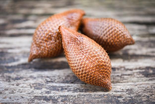 Salak na drewnianym tle - salak tropikalny owoc salacca zalacca lub wąż owocowa palma