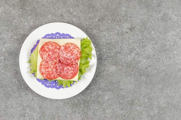 Salami pokrojone w plasterki na białym talerzu z serem i sałatą