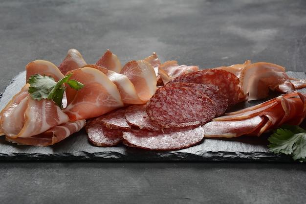 Salami, prosciutto, boczek na desce do krojenia. asortyment wędliniarski wędlin