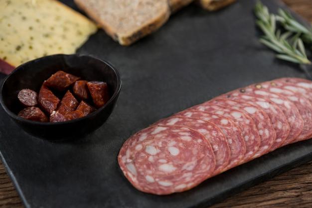 Salami, ser i kromki ciemnego chleba na talerzu łupkowym