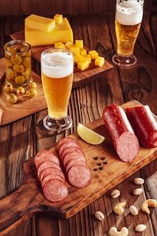 Salami wędzone w plasterkach z dwiema szklankami piwa, młodymi serami, oliwkami, kasztanami i pistacjami