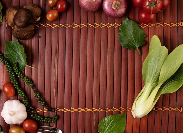 Sałata kantońska, pestki świeżej papryki, czosnek, pomidory, grzyby shiitake i czerwona cebula ułożone na drewnianych deskach