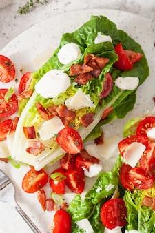 Sałata romaine zwieńczona parmezanem, bekonem i sosem pomidorowym. zdrowy lunch diety keto paleo