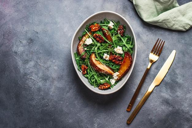 Salaterka z rukolą, pieczoną gruszką, orzechami, twarogiem i miodem przeszukana na niebieskiej kamiennej ścianie ze złotym widelcem i nożem. koncepcja zdrowego odżywiania. flatlay z copyspace. żywność dla wzmocnienia odporności