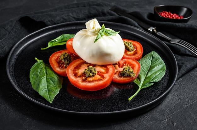 Sałatka burrata i sałatka pomidorowa podana na czarnym talerzu. ciemne tło widok z góry