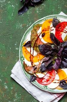 Sałatka caprese plasterki pomidora i mozzarelli z liśćmi bazylii