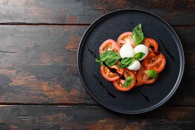 Sałatka caprese z plastrami pomidorów, mozzarellą, bazylią, oliwą