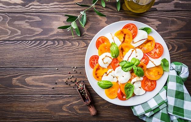 Sałatka caprese z sera mozzarella, żółtych pomidorów i liści bazylii na drewnianej powierzchni. widok z góry.