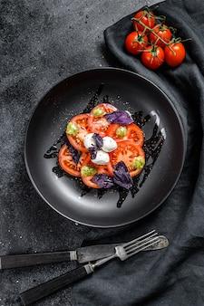 Sałatka caprese. zdrowy posiłek z pomidorami koktajlowymi, kulkami mozzarelli i fioletową bazylią. koncepcja smacznego i zdrowego wegetariańskiego posiłku. czarne tło. widok z góry