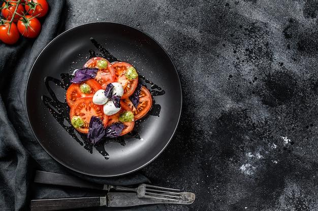 Sałatka caprese. zdrowy posiłek z pomidorkami koktajlowymi, kulkami mozzarelli i fioletową bazylią. pomysł na smaczny i zdrowy posiłek wegetariański. czarne tło
