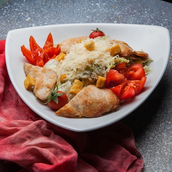 Sałatka cesarska z pomidorem i szmatką w trójkątnym talerzu