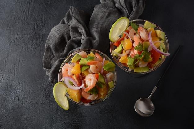 Sałatka ceviche z krewetkami, pomarańczami i awokado w szklanej misce na ciemnym lub szarym tle. jedzenie w ameryce łacińskiej. pyszne, świeżo przygotowane ceviche z krewetkami. krewetki marynowane w limonce i pomarańczy .