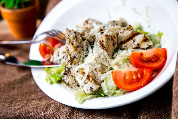 Sałatka cezar kurczak pomidor sałata parmezan sardele widok z boku