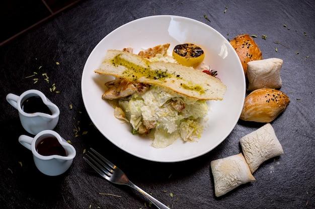 Sałatka cezar kurczak sałata pomidor cytryna parmezan anchois bułeczki widok z boku
