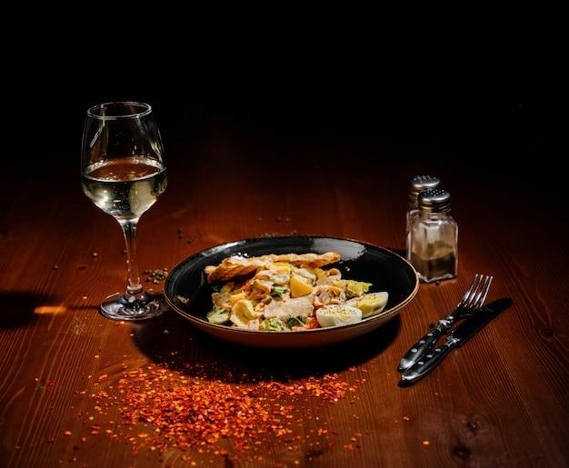 Sałatka cezar na czarnym talerzu na drewnianym stole.