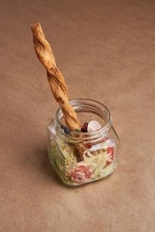 Sałatka cezar podawana w szklanym słoju.
