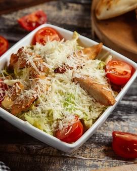 Sałatka cezar z grillowanym filetem z kurczaka, serem i pomidorami.