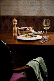 Sałatka cezar z grzankami, jajkiem przepiórczym, pomidorkami koktajlowymi i grillowanym kurczakiem na drewnianym stole