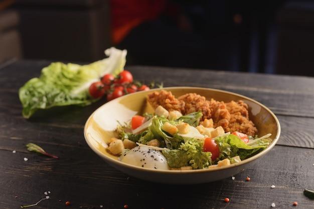 Sałatka cezar z kurczakiem, jajkiem, parmezanem i warzywami. w żółtym talerzu na drewnianym stole