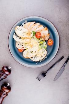 Sałatka cezar z kurczakiem, ozdobiona pomidorami koktajlowymi, ozdobiona czarnymi sztućcami. koncepcja menu restauracji lub zdrowej diety.