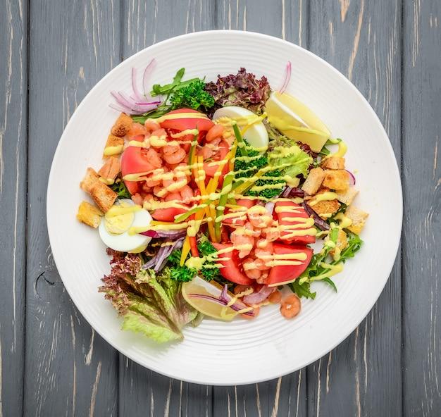 Sałatka cezar z owocami morza z krewetkami, liściem sałatki, grzankami, serem pomidorowym