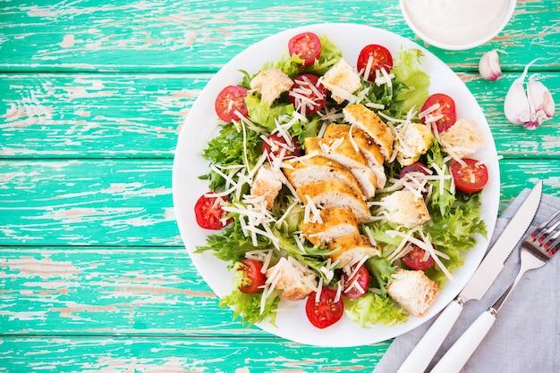 Sałatka cezar z piersią kurczaka na rustykalnym tle, pomidorami, parmezanem, zieloną sałatą i grzankami, selektywne focus, kopia przestrzeń