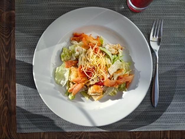 Sałatka cezar z prosciutto gotowym do spożycia. widok z góry. sałatka cezar na białym talerzu na restauracyjnym blacie. naturalne modne, intensywne światło dzienne