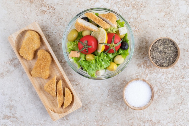 Sałatka cezar z ziołami, warzywami i nuggetsami z kurczaka.