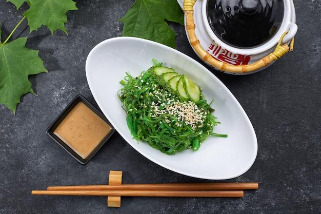 Sałatka chuka z ogórkami, sezamem i sosem, na białym talerzu, z japońskim czajnikiem, pałeczkami i liśćmi klonu, na czarnym betonie