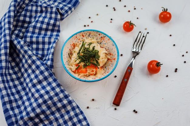 Sałatka colesław w misce na białym stole. biały stół zdobi niebieski ręcznik, pomidory, widelec.